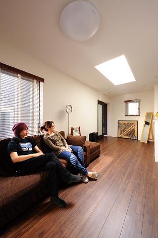 幸和ハウジング【デザイン住宅、趣味、ガレージ】天窓部分を勾配天井に したため広い範囲に光 が差し込む明るいリビン グダイニング。アンティー ク感漂うフローリングとド アは幸和ハウジングのオ リジナルでご主人もお気 に入り