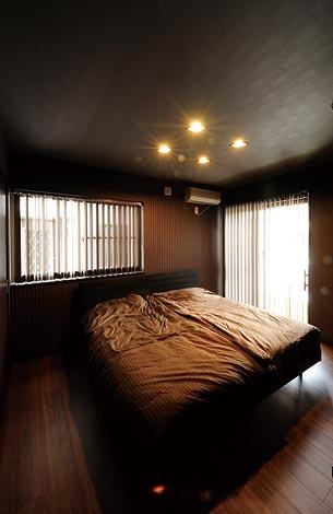 幸和ハウジング【デザイン住宅、趣味、ガレージ】ダークブラウンを基調 としたシックな寝室。 照明に映えるストライ プの壁紙がポイント