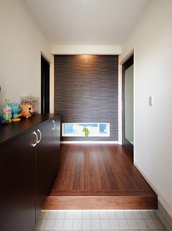 幸和ハウジング【デザイン住宅、趣味、ガレージ】玄関正面にタイル 壁を採用。照明に よる陰影が高級感 を醸し出す