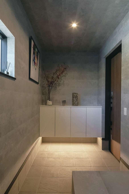 幸和ハウジング【デザイン住宅、趣味、屋上バルコニー】床と天井、土間をグレーで統一したスタイリッシュな玄関。足元の間接照明が土間の素材感を引き立てる