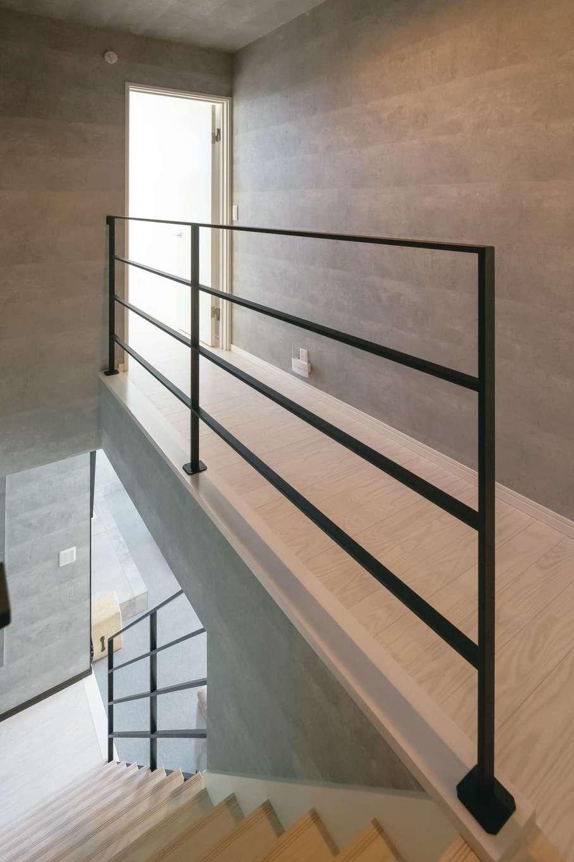 幸和ハウジング【デザイン住宅、趣味、屋上バルコニー】階段の吹抜け。廊下の手すりのアイアンの繊細なフォルムが洗練された空間を演出。2階の廊下も壁をグレーで統一してある