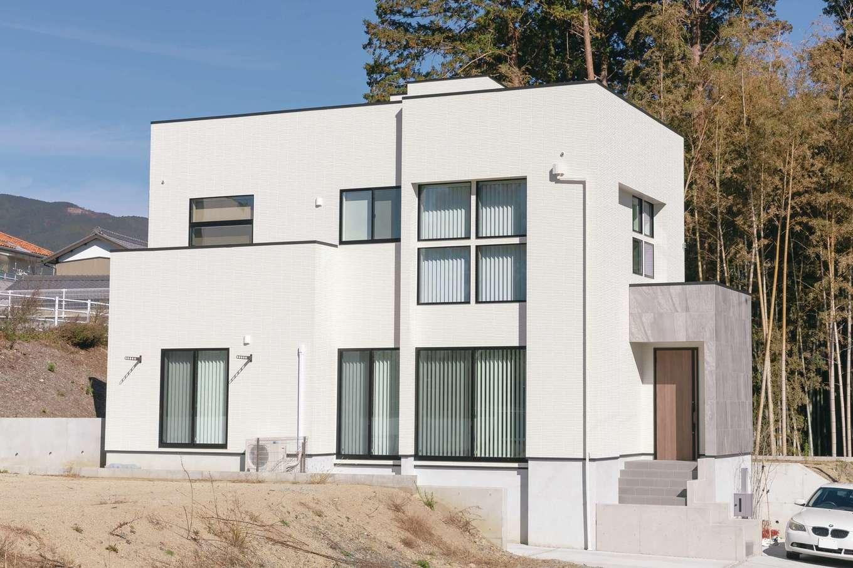 幸和ハウジング【デザイン住宅、趣味、屋上バルコニー】白をベースに玄関ポーチのグレーの外壁が映える外観。窓の配置が個性を醸し出している。屋上にはスカイテラスがある