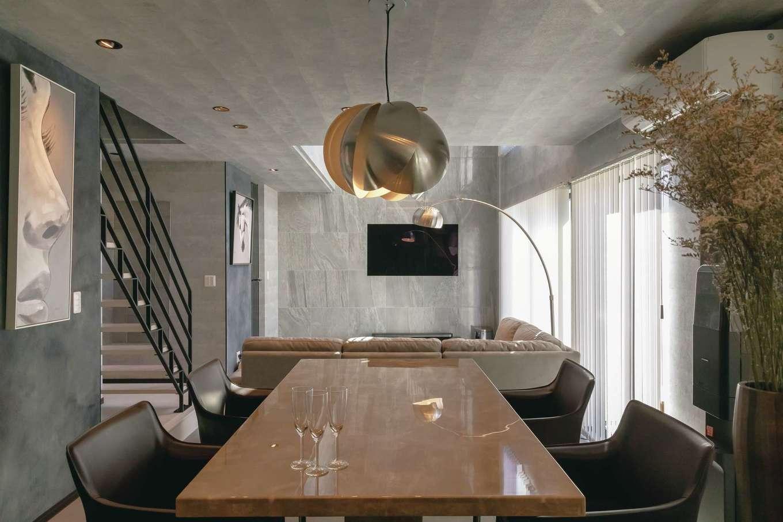 幸和ハウジング【デザイン住宅、趣味、屋上バルコニー】アイランドキッチンの真正面にダイニングテーブルを設置。ペンダント照明はご主人のこだわり。壁面の絵を飾った壁は塗り壁にしてスポット照明を設けてある