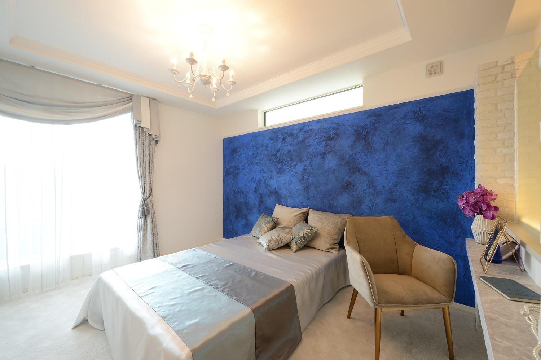 幸和ハウジング【浜松市西区入野町6149-1・モデルハウス】背景の青が映える寝室。ラグジュアリーな雰囲気のなかでも、リラックスできる空間に仕上げた