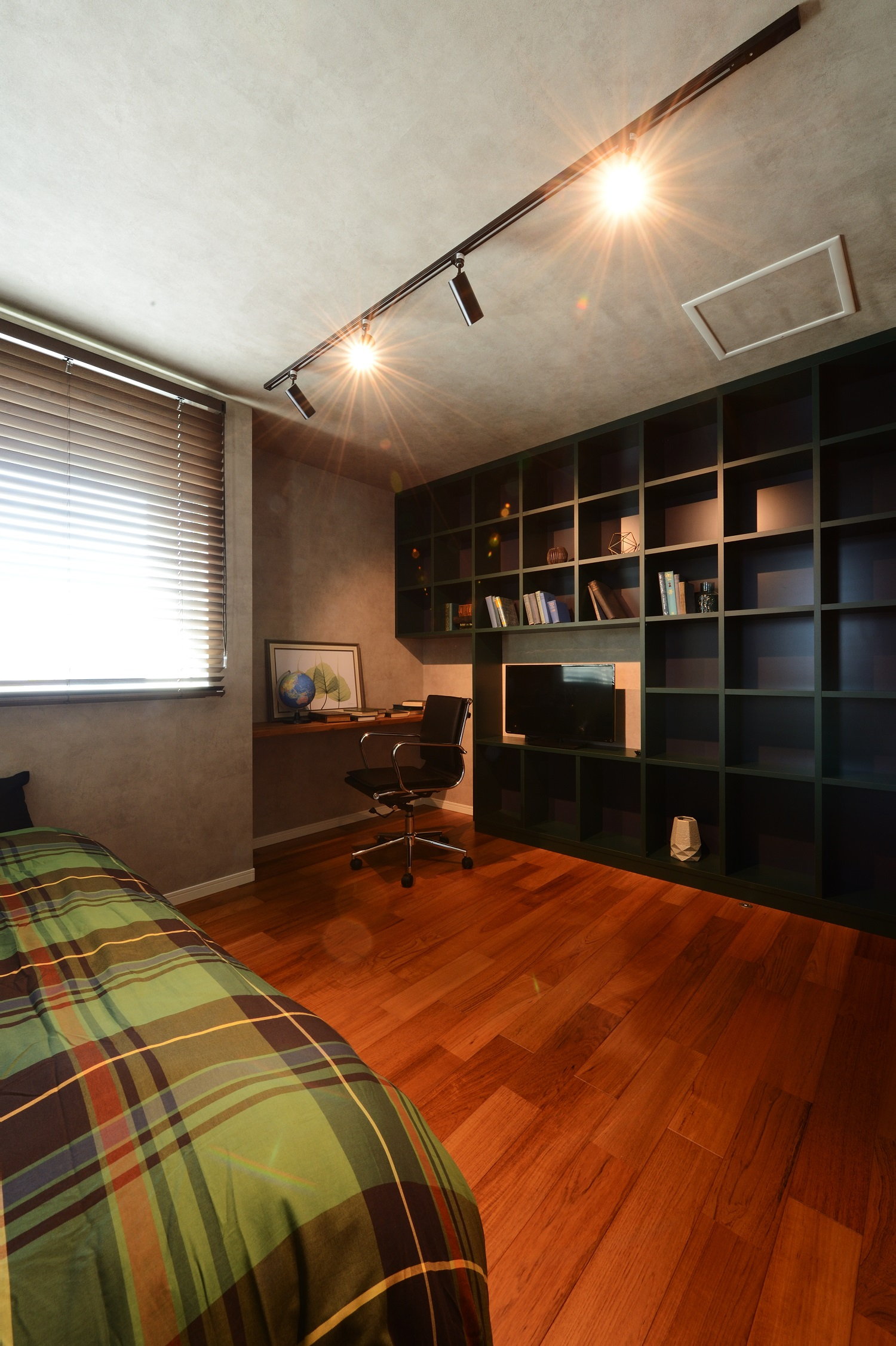 幸和ハウジング【浜松市西区入野町6149-1・モデルハウス】黒の壁面収納がシックな雰囲気を醸し出す2つ目の寝室。寝る前に読書を楽しむ