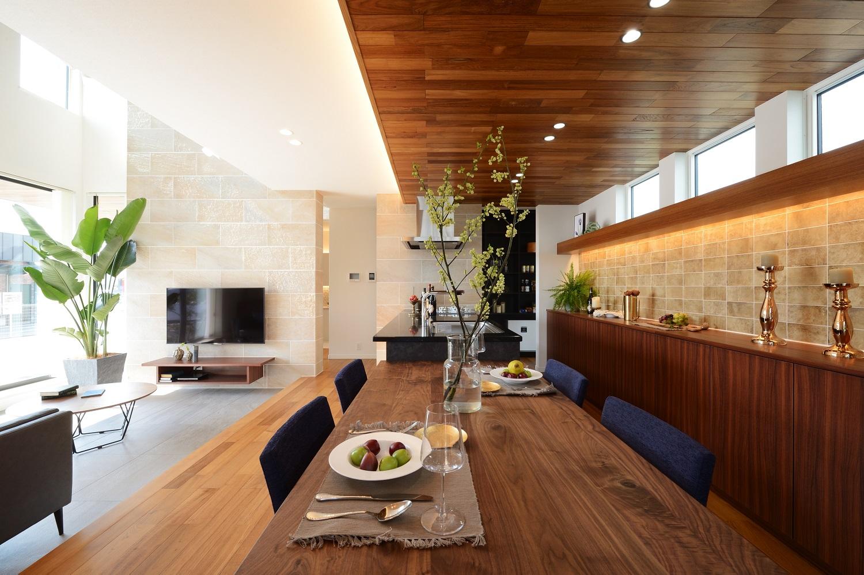 幸和ハウジング【浜松市西区入野町6149-1・モデルハウス】リビングから小上がりでつながるキッチン。白い壁と木材のコントラストがうまく調和している