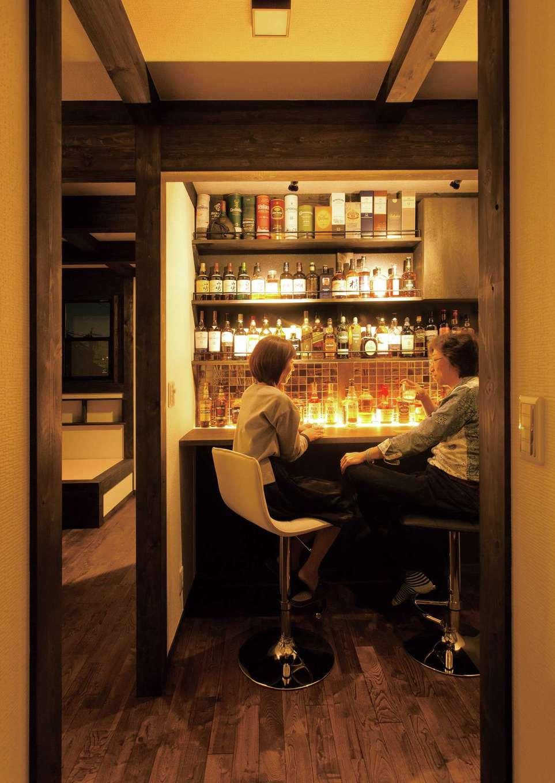 サイエンスホーム【1000万円台、趣味、自然素材】2階フリースペースの一角に設けたショップ仕様のバーカウンター。ウイスキーが映えるよう壁面はブラックに、カウンターの間接照明で上質感を演出。夫婦でしっぽり宅呑みしたり、友人を招いて大好きなウイスキーを楽しみたいという夢が実現した