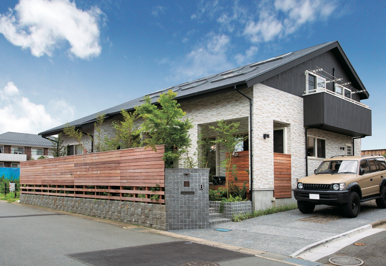 サイエンスホーム【デザイン住宅、自然素材、省エネ】大屋根のモダンな外観デザインはご夫妻のお気に入り。人通りの激しい商店街という立地条件から、ワイドスパンの格子や植栽で目隠しを