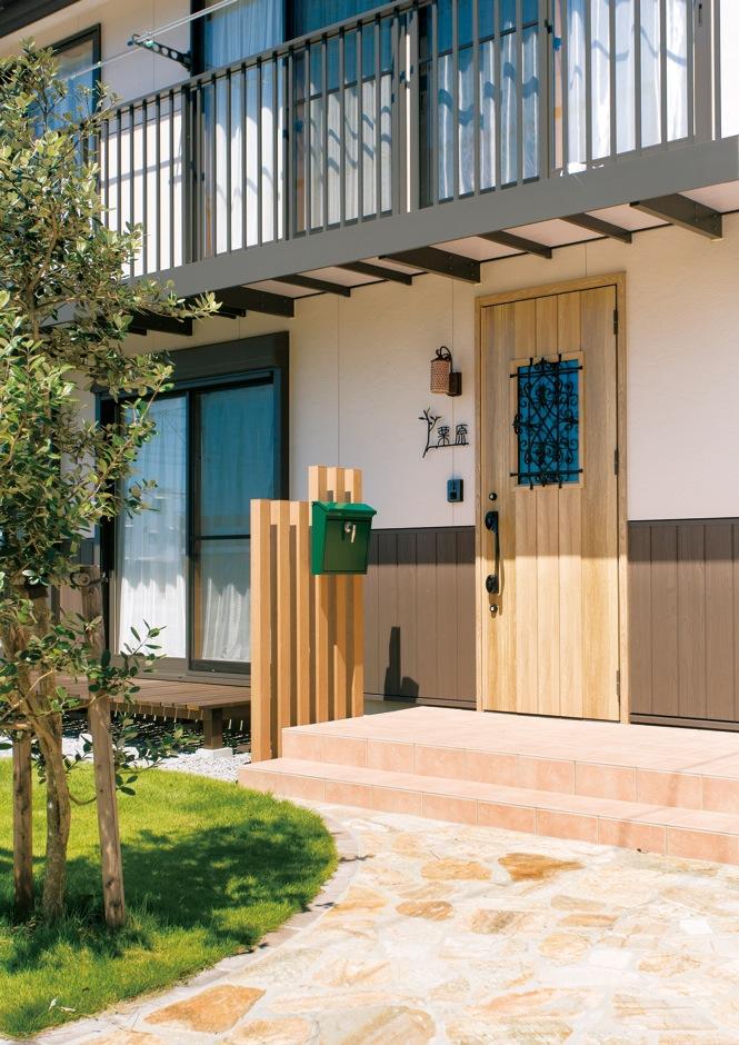 サイエンスホーム【趣味、省エネ、間取り】敷き詰めたレンガや木製のドアがかわいらしい玄関まわり。芝生のグリーンがアクセント