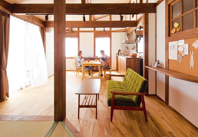 勾配天井に組んだ梁組みが真壁造りの魅力を強調。対面式のキッチンからはリビン グや畳コーナーはもちろんのこと、テラス越しに子ども室まで見渡せる