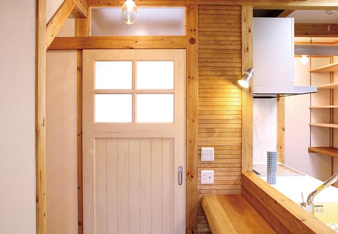 サイエンスホーム【1000万円台、収納力、自然素材】玄関に通じるドアをホワイトのカントリー調にして、ウッディな広い空間にアクセントを付けた