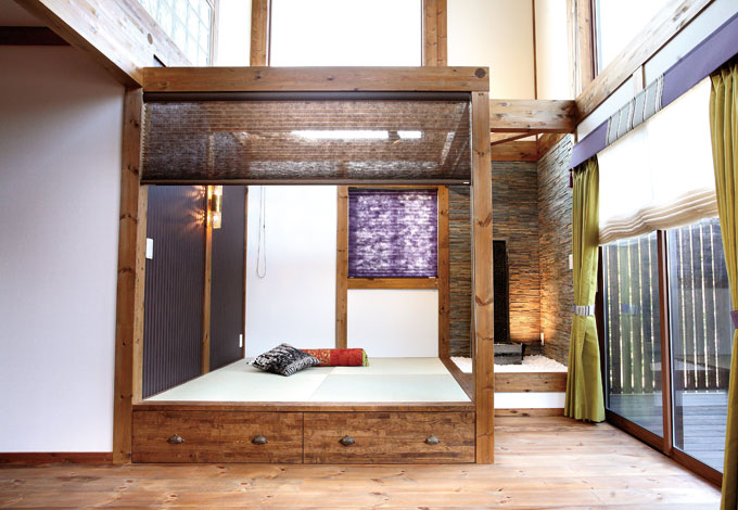 吹き抜けの真下に設けた畳コーナー。天井のない開放的な空間は午後の「シエスタ」にも最適。プレーンシェードや和紙のブラインドでリゾート感を演出している。小上がりの段差部分は収納スペース。