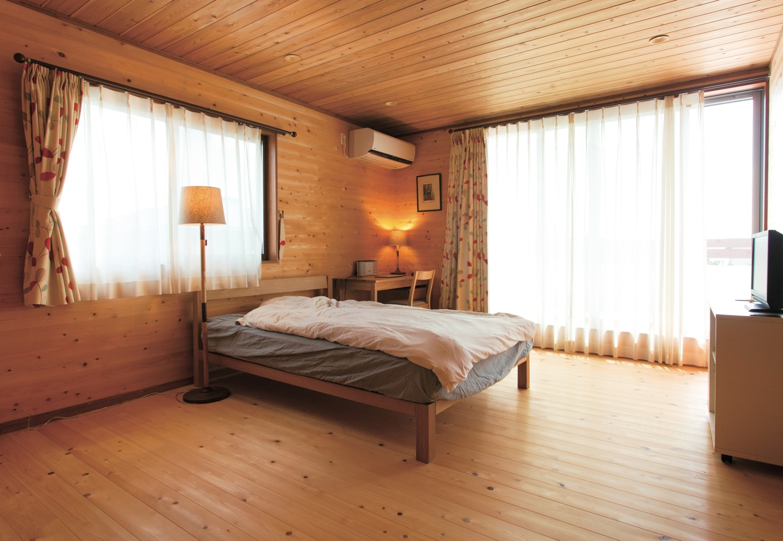 寿建設【収納力、自然素材、間取り】ログハウスのような主寝室。窓を開ければ家族全員の布団を一気に干せる広大なバルコニーと直結