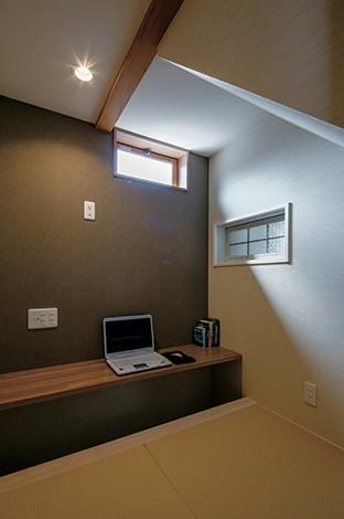 """寿建設【収納力、間取り、スキップフロア】階段下のデッドスペースは収納にするケースが多いが、ご主人の希望で書斎になった。2畳の空間はまさに""""男の隠れ家""""。掘りごたつのカウンター、書棚は造作。右手のガラス窓は、工房の気配を感じられるようにと設置"""