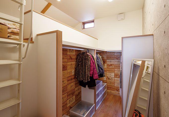 寿建設【収納力、間取り、スキップフロア】主寝室の隣に設けた4畳のウォークインクローゼット。ワインの木箱や打ちっ放しのコンクリートをデザインしたユニークなクロスで遊び心も抜群。広いロフトもあるので、どんなに荷物が増えても安心