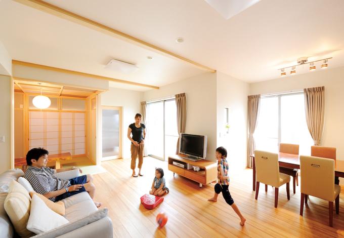 寿建設【デザイン住宅、子育て、自然素材】明るいLDKは和室、ウッドデッキともつながる。松の床の上で子どもたちも大はしゃぎ