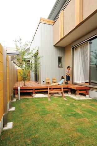 寿建設【デザイン住宅、子育て、自然素材】お庭にはウッドデッキも砂場もあるよ! 広いウッドデッキではみんなで朝食を楽しんだり、パパと遊んだり。ジューンベリーの木が家族をやさしく見守る