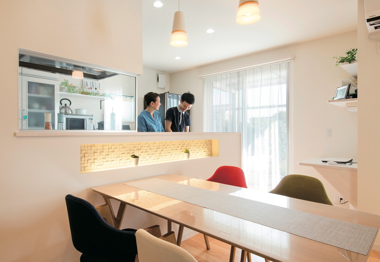 コットンハウス【デザイン住宅、省エネ、平屋】一緒に料理をつくる仲睦まじいTさん夫妻。キッチン横のドアを開けると、洗濯物を干せるテラスとつながる
