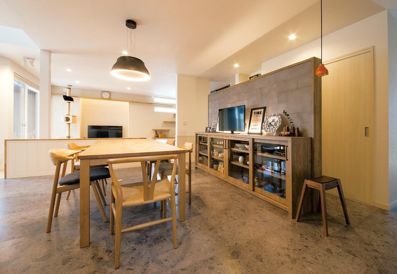 コットンハウス【収納力、省エネ、ペット】家族の団欒の中心はダイニング。大テーブルも飾り棚も部屋の雰囲気に合わせて作ったオーダーメイド。家具の木目が引き立つように、床にはグレーのフロアタイルを使用