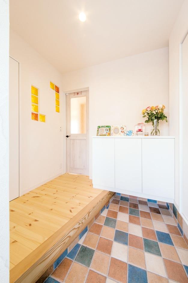 コットンハウス【デザイン住宅、省エネ、インテリア】白がベースの空間にカラフルな土間のタイルが映える玄関。壁面のガラスブロックは奥さまの好きな黄色 ×オレンジを採用