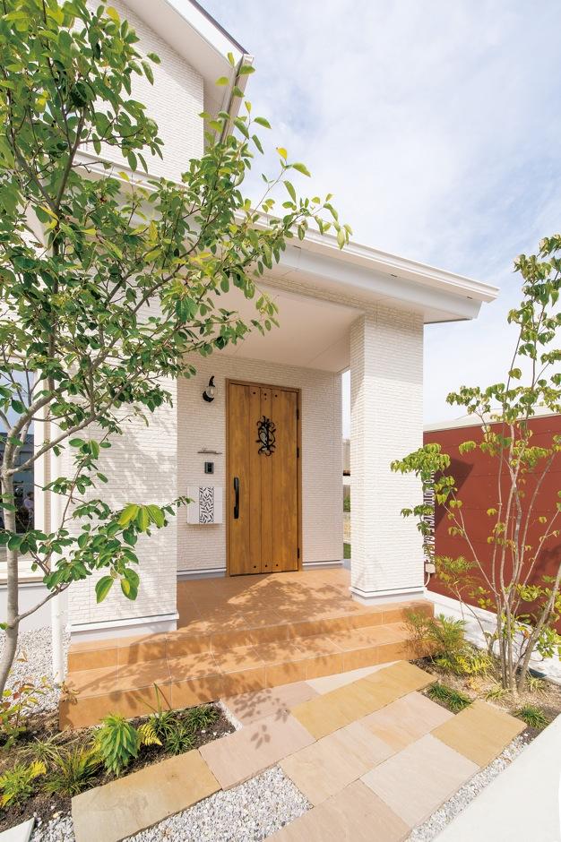 コットンハウス【子育て、収納力、間取り】白い外壁にシンボルツリーの緑が映えるオシャレな玄関ポーチ