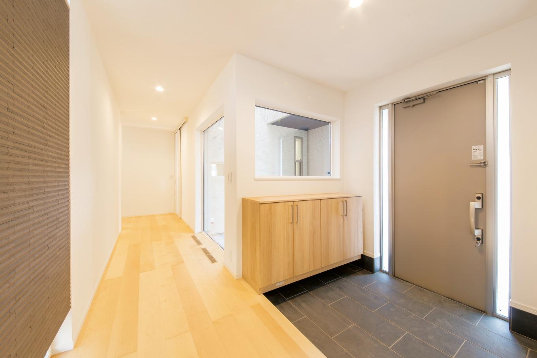 コットンハウス【子育て、収納力、省エネ】玄関の横には坪庭があり、室内に明るさと開放感をもたらしている。正面のグレーのアクセントウォールがシンプルな空間を引き締めている