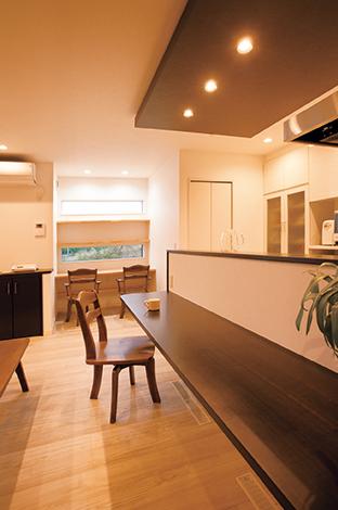 コットンハウス【デザイン住宅、収納力、趣味】5人が並んで食事できる広々カウンター。天井のアクセントクロス×ダウンライトがオシャレなバーの雰囲気を演出