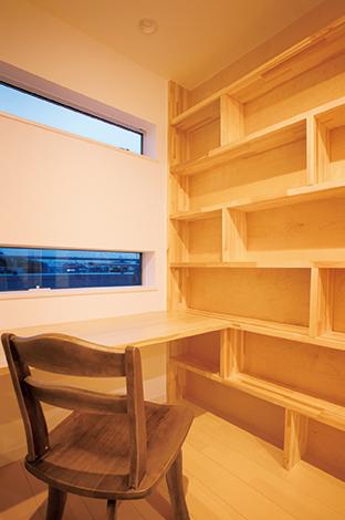 コットンハウス【デザイン住宅、収納力、趣味】家族共有のフリースペースには、カウンターと書棚を壁一面に設置。子ども部屋は3姉妹共有の寝室として利用するだけで、普段はここで勉強したり、本を読んだり。家族のコミュニケーションが深まる空間