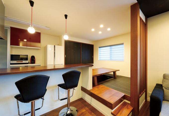 コットンハウス【デザイン住宅、子育て、輸入住宅】カウンターキッチンに掘りごたつ式のテーブルをセッティングした居酒屋風のダイニング。ステップを設けたことで、リビングとのメリハリがつく