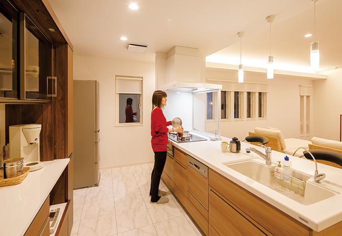 コットンハウス【デザイン住宅、狭小住宅、屋上バルコニー】存在感たっぷりのアイランドキッチンは、家族みんなが自然に集まって来る。広いキッチンカウンターは、配膳もお片づけもスムーズで、奥さまの負担を軽減