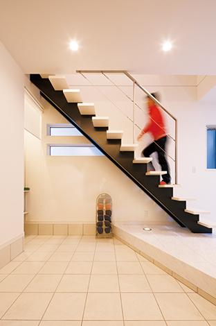 """コットンハウス【デザイン住宅、狭小住宅、屋上バルコニー】ギャラリーのような凛とした雰囲気がただよう玄関ホール。スケルトンの階段が空間をより広く見せる。""""広い""""空間はご主人のこだわり"""