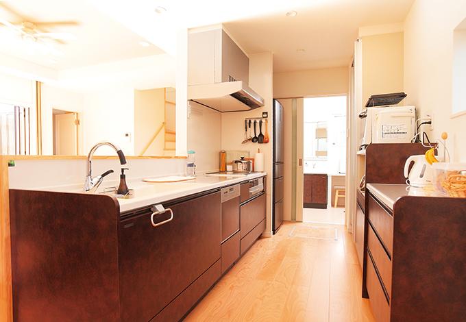 コットンハウス【デザイン住宅、子育て、趣味】白を基調としたリビングに対して、キッチンと洗面台はレザー調のパネルで高級感を演出。広い作業スペースと洗面、浴室へのストレートな動線も便利