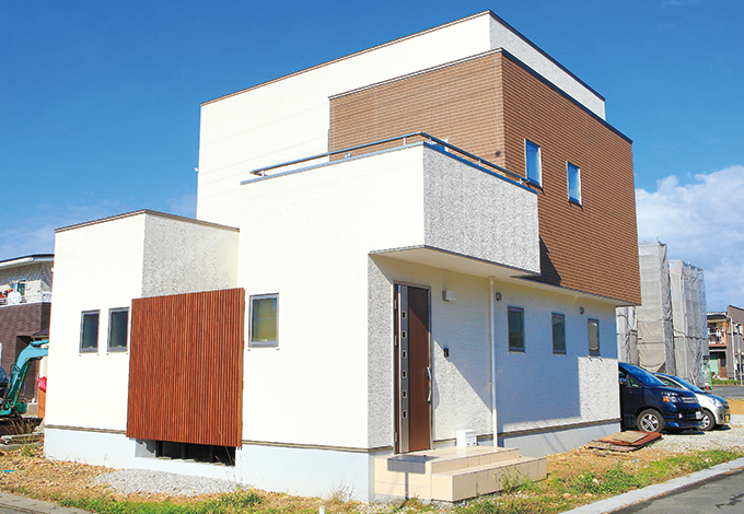 コットンハウス【デザイン住宅、子育て、趣味】キューブを重ね合わせたようなシンプルな外観もご夫婦のこだわり。白い壁に木の格子がアクセントに