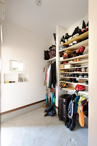 コットンハウス【二世帯住宅、自然素材、省エネ】玄関からつながる土間収納は扉を設け、中はあえて棚板だけ通したオープン収納に。家族5人の靴をすっきり納め、コートもひと目で見渡せる。明り取りの小窓やニッチで遊び心をプラス