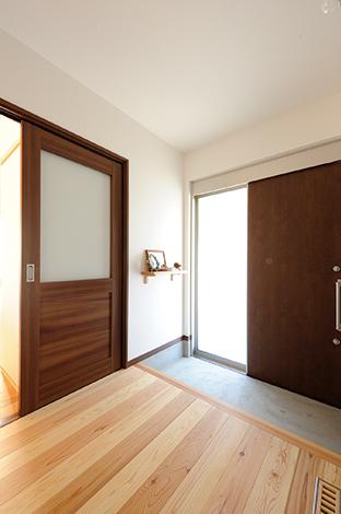 コットンハウス【二世帯住宅、自然素材、省エネ】西向きの玄関が暗くならないよう引き戸の片側を明り取りに。木製の建具と床板のコントラストも◎