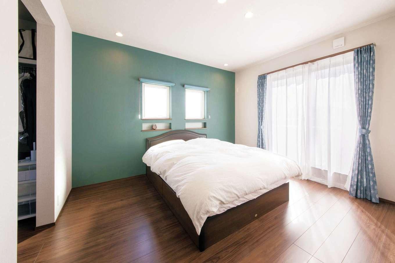 コットンハウス【趣味、省エネ、間取り】寝室は、ペールブルーのアクセントクロスと濃い茶系のフロアがマッチして落ち着きのある洗練された空間を実現。カーテンもクロスと同色でコーディネート。ウォークインクローゼットは収納力が抜群