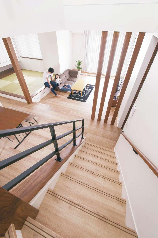 コットンハウス【子育て、省エネ、間取り】階段から眺めたリビング。構造上必要な柱をアクセントに活かしている。アイアンの手すりは夫妻のこだわりポイント