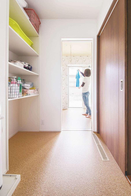 コットンハウス【子育て、省エネ、間取り】洗面スペースの奥にはランドリールームがあり、雨天でも除湿機+サーキュレーターで室内干しが1日でしっかり乾く。その先にはテラスがあり、晴れた日の外干しも短い動線で効率良くできる