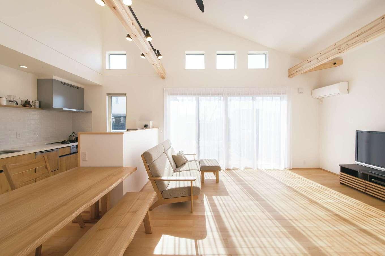 コットンハウス【子育て、省エネ、間取り】屋根勾配を活用した伸びやかで明るいLDK。高窓は視線を気にせず採光できるのが利点。照明を設置するために飾り梁を渡し、キッチン壁はタイルで上品に仕上げた