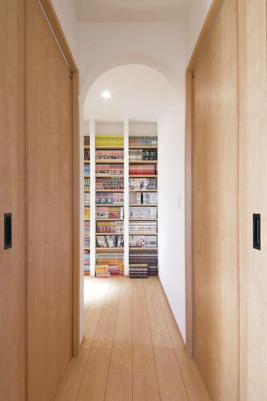 コットンハウス【子育て、省エネ、間取り】2階の納戸はコミック本が大好きなご主人の蔵書を収納するライブラリーに。造り付けの本棚は地震でも倒れる心配がない。アーチ型の入り口がアクセント
