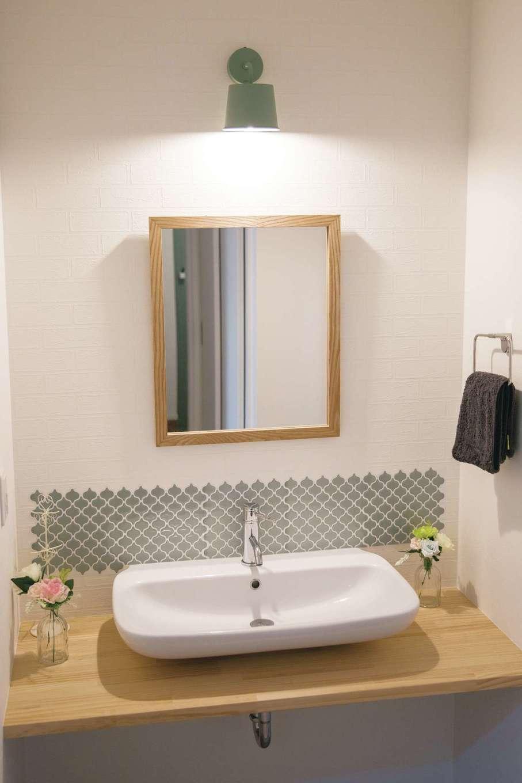 コットンハウス【子育て、省エネ、間取り】玄関の突きあたりにある洗面スペース。帰宅してから手を洗ってLDKへ…という効率的な動線を確保。奥さまが壁にタイルのシールを貼ってオシャレに演出