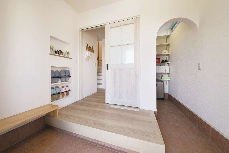 コットンハウス【子育て、省エネ、間取り】玄関は土間をL字型に設けてシューズクロークを確保。R型の出入口がかわいらしい。ベンチやスリッパラックなど、使い勝手もしっかり重視されている