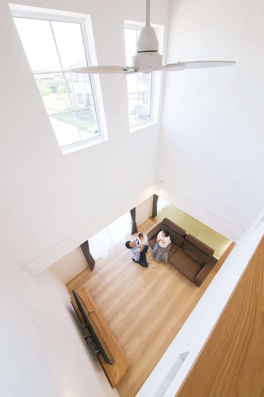 コットンハウス【子育て、省エネ、間取り】吹抜けから眺めるLDK。ハイブリッド断熱により、広い吹抜け空間でも家中が年中快適に。高窓からLDKに光が注ぐ