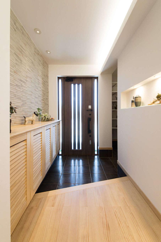 コットンハウス【浜松市西区篠原町21561・モデルハウス】シューズクロークと玄関収納を備え、収納をたっぷり確保した玄関。間接照明付きのニッチにはお気に入りの小物やグリーンを飾って