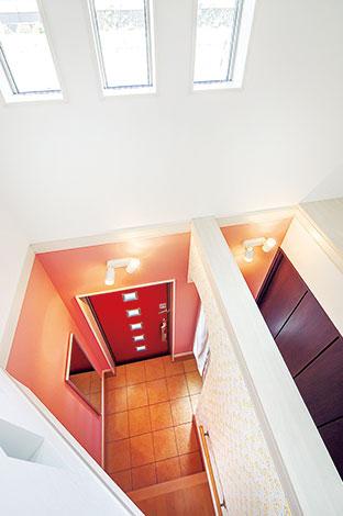 Mulberry House 桑原建設【デザイン住宅、収納力、間取り】2階から眺めた吹抜けの玄関。ピンク色の壁と赤いドアの組み合わせが可愛らしく優しい雰囲気