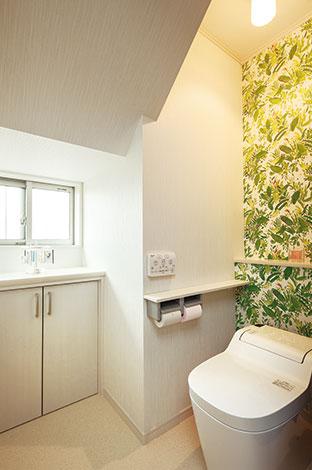 Mulberry House 桑原建設【デザイン住宅、収納力、間取り】L字型のトイレの奥はリーフ柄のクロスでさわやかに演出