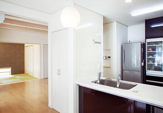 Mulberry House 桑原建設【デザイン住宅、収納力、間取り】リビングとダイニングを壁でゾーニングLDKを全てオープンにするのではなく、キッチンの側面に壁を設けることでリビングとダイニングをゾーン分けし、あえて見え隠れする空間を創出。少し奥まったダイニングはプライベートな落ち着きを感じさせゆったりくつろげる。リビングで接客中でも他の家族の居場所を確保でき、余計な物も隠しておけて便利。