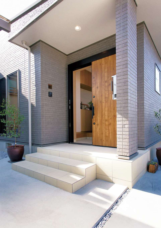 かなめ創建【自然素材、省エネ、間取り】シックな外壁に、木製のドアが映える玄関ポーチ