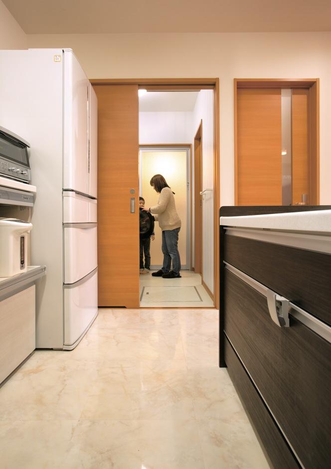 かなめ創建【子育て、狭小住宅、インテリア】キッチンの床はタイルを張って、ダイニングとの変化をつけた。見た目よりも冷たくない。サニタリーへの短い動線は『かなめ創建』の女性一級建築士、松野さんからの提案