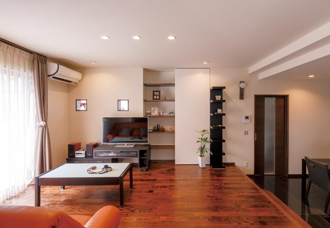 かなめ創建【デザイン住宅、省エネ、間取り】開放感あふれるリビングの床は無垢のクルミ。特許取得の「落とし蓋工法」によって、耐震性とともに遮音性も抜群。テレビのバックヤードは、片面扉を採用し、見せる収納と隠す収納を実現